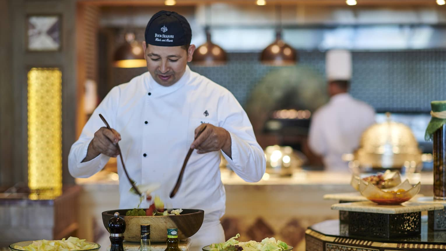 Chef tosses salad at buffet station with chopped vegetables in bowls