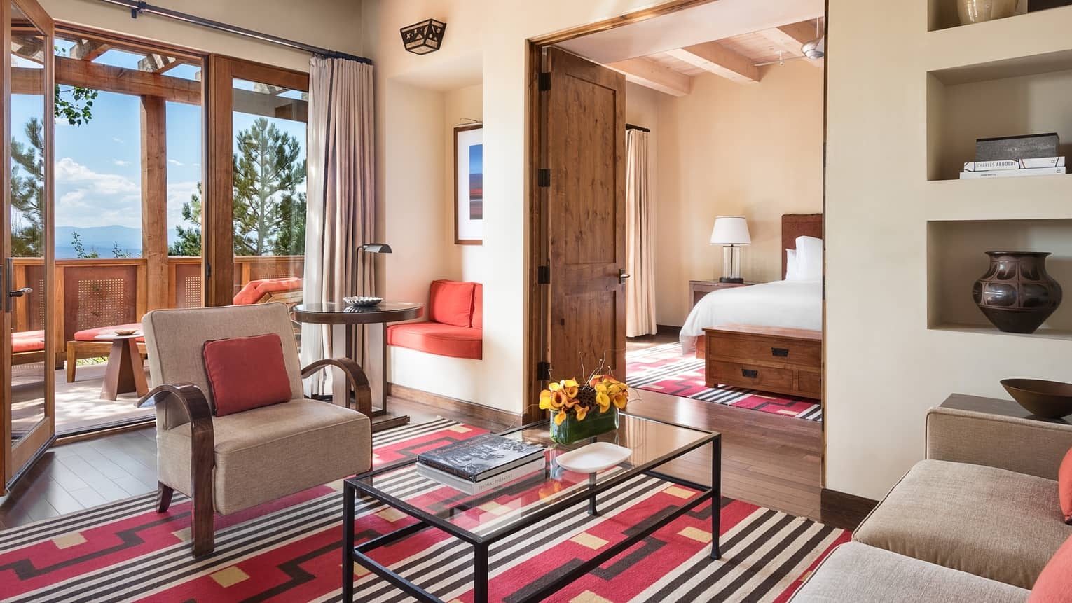 Sunset Suite living room, Southwestern-style rug, wood doors to balcony, bedroom
