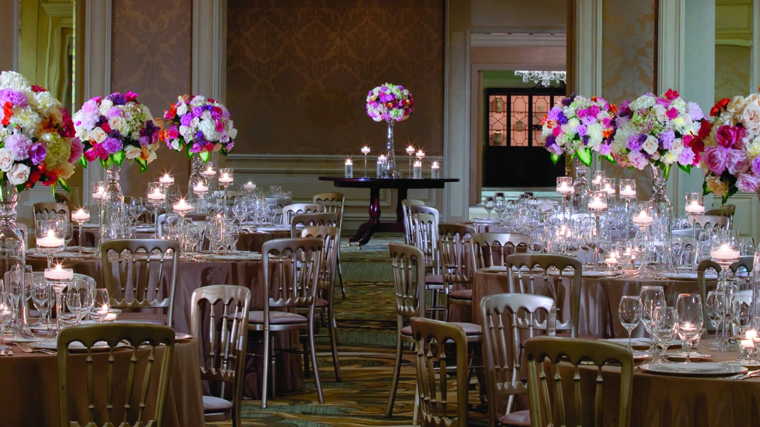 Tall pink and white floral arrangements on small round banquet tables with crystal glassware