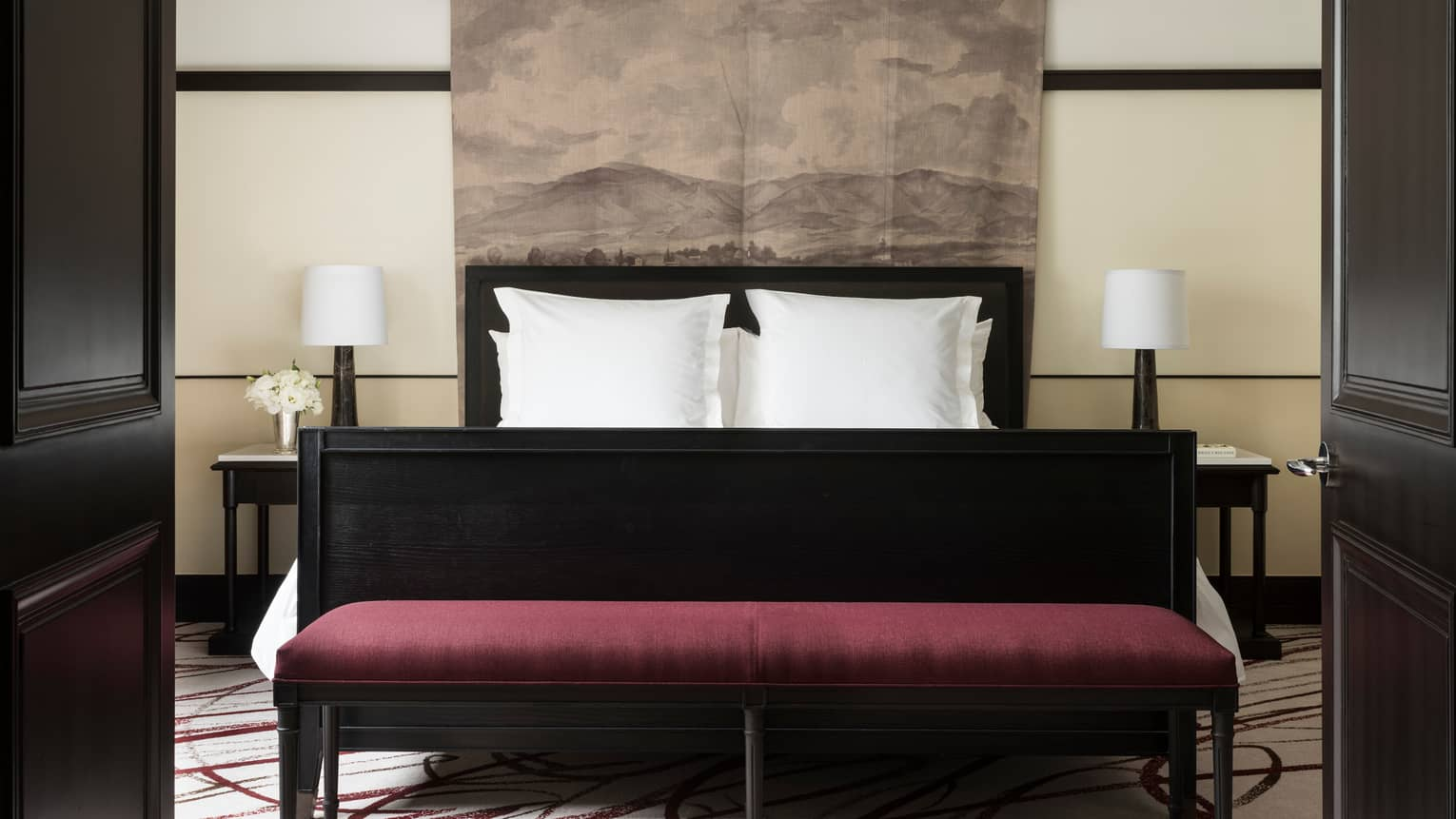 Open black French doors revealing Executive Suite bed, burgundy velvet bench at foot