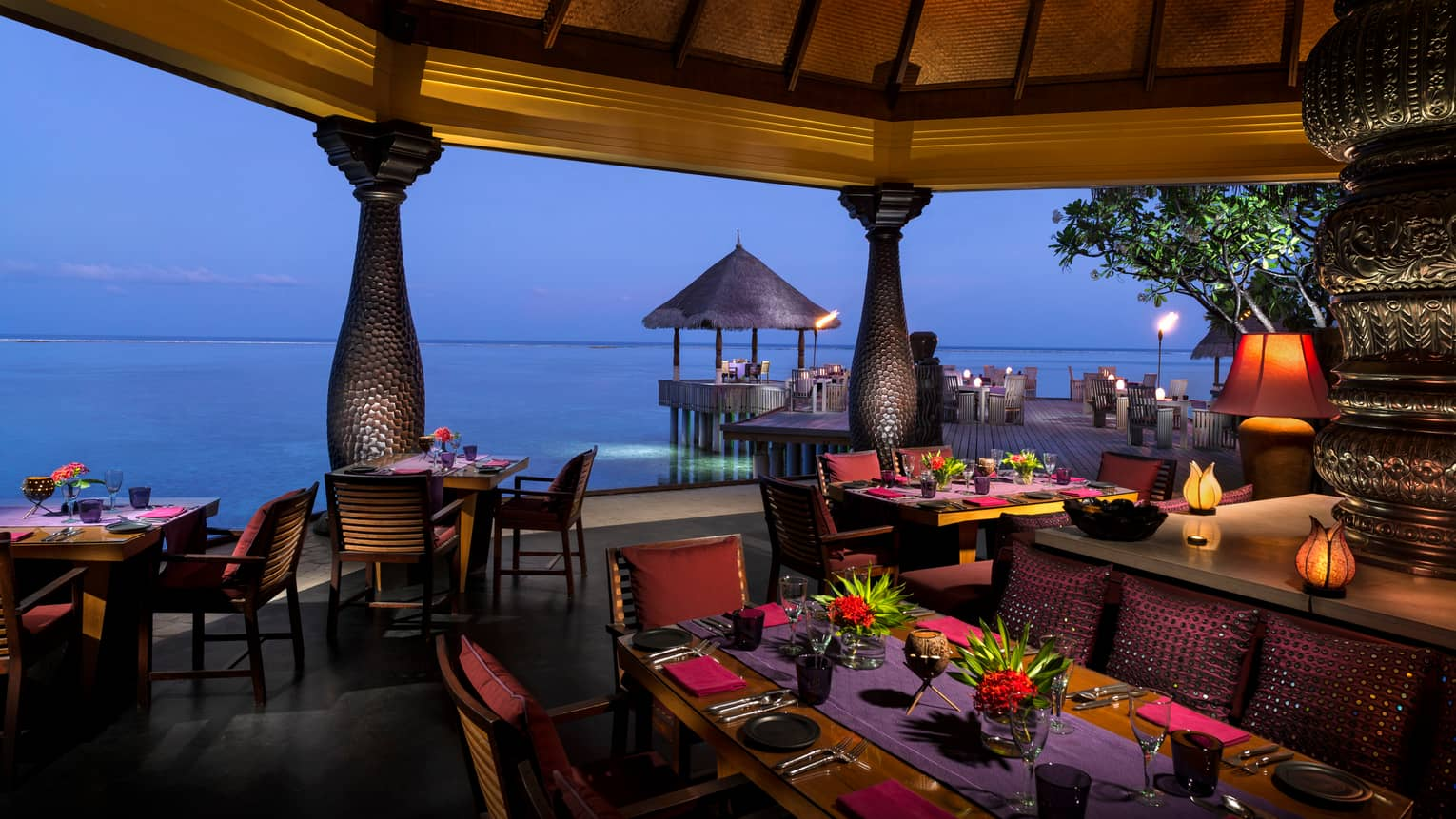 Evening view of Baraabaru restaurant dining patio on the water, with tropical flower arrangements, lanterns