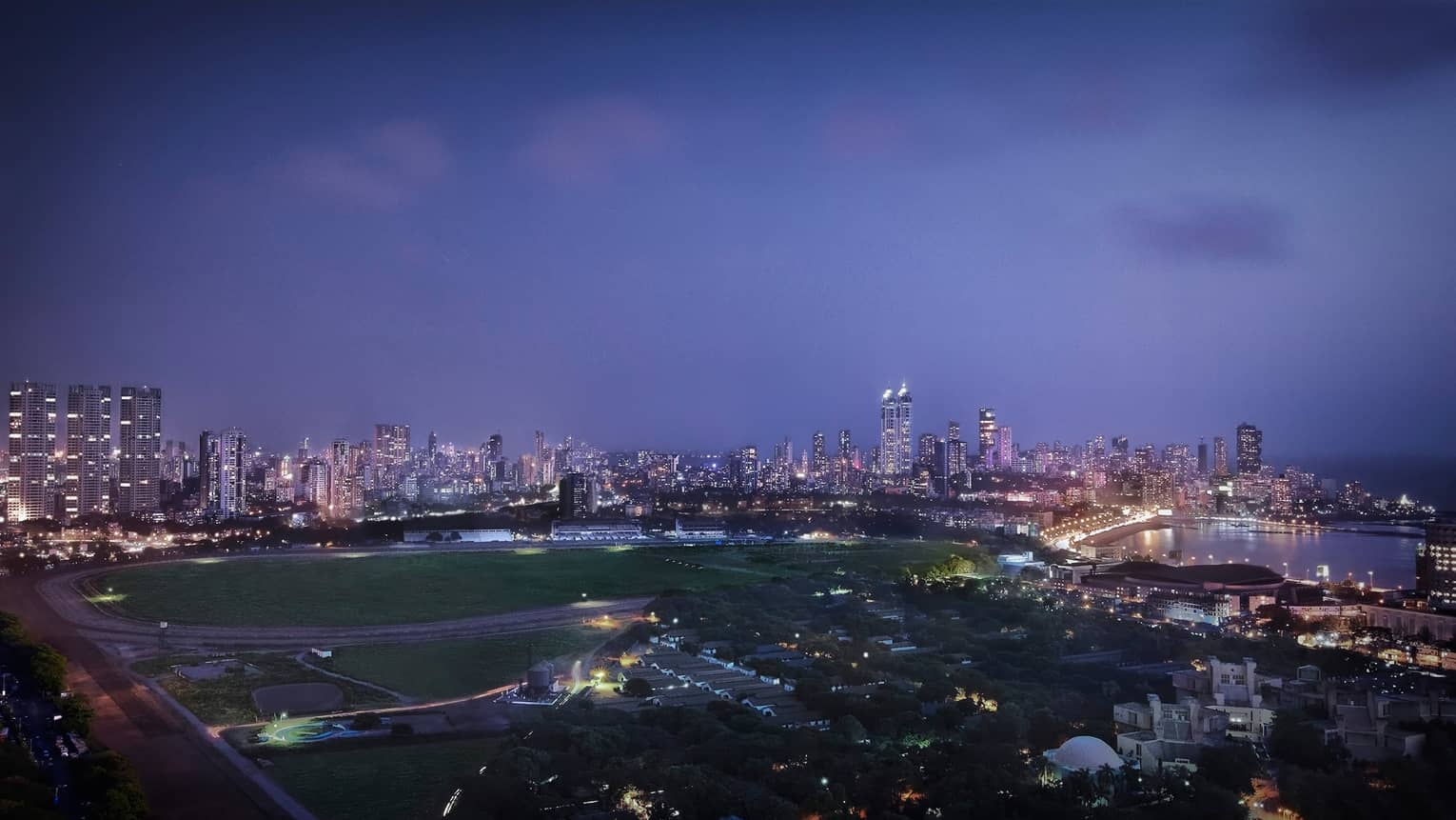View over large field, track, Mumbai city skyline with buildings, lights at dusk