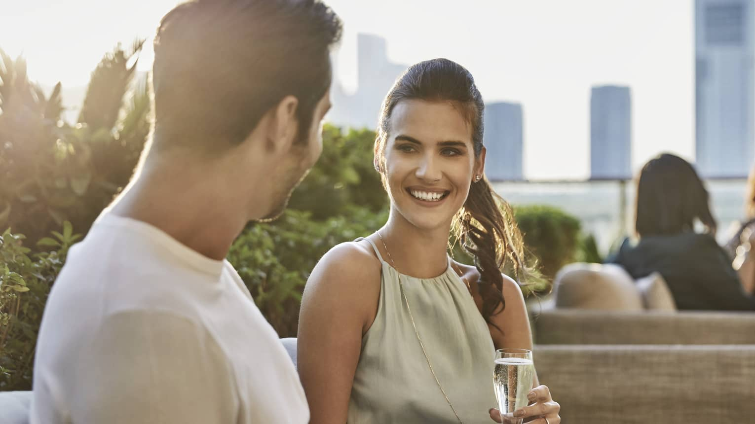 A man and woman enjoy and glass of champagne, sitting side by side on a bench at four seasons hotel abu dhabi meylas terrace.