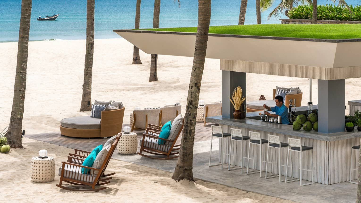 Bartender mixes drink at square stand-alone Beach Bar gazebo under palms on white sand