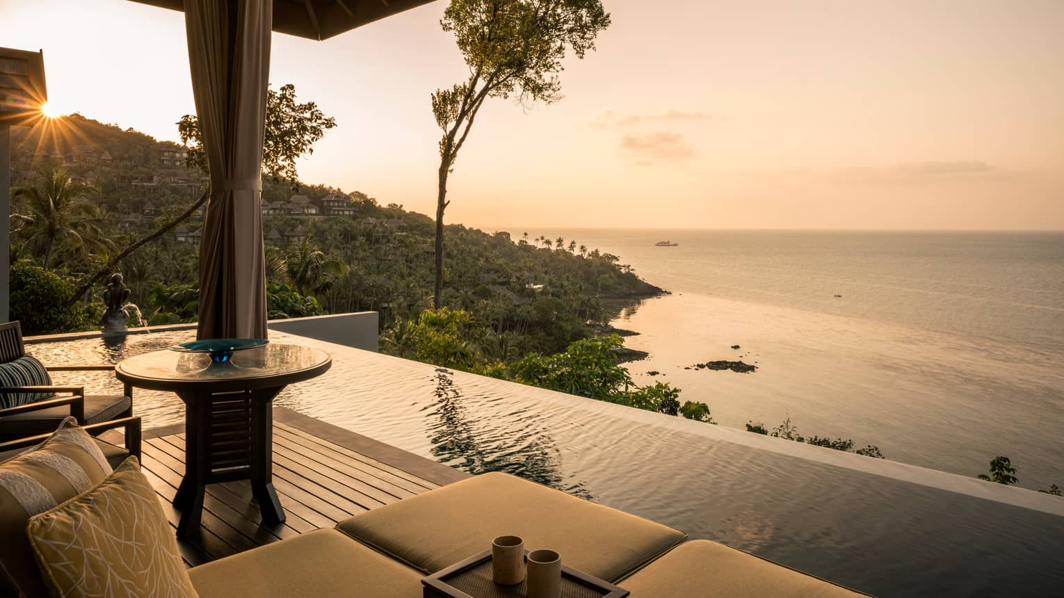 One-bedroom pool villa patio chair, infinity pool overlooking mountain, ocean at sunset