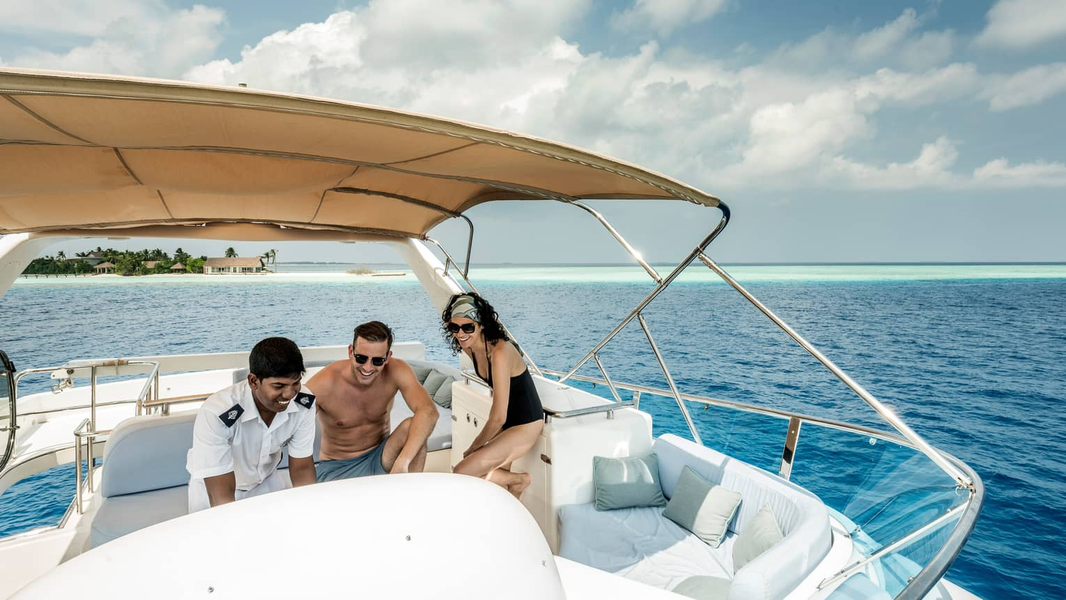 Couple sits at console with captain on Voavah Summer boat