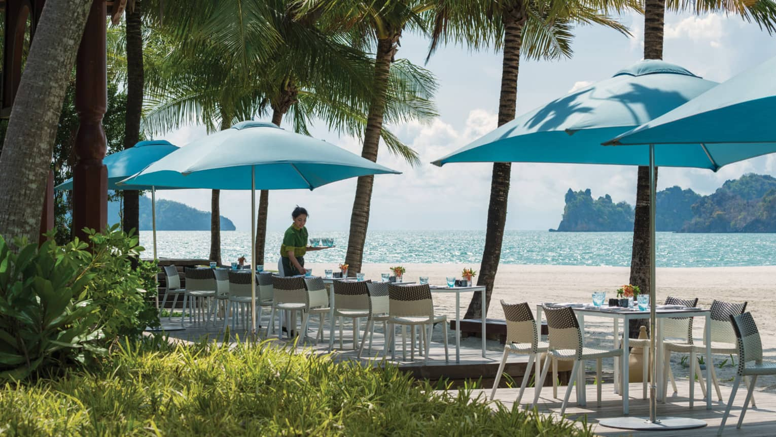 Server sets patio dining tables under blue umbrellas along beach