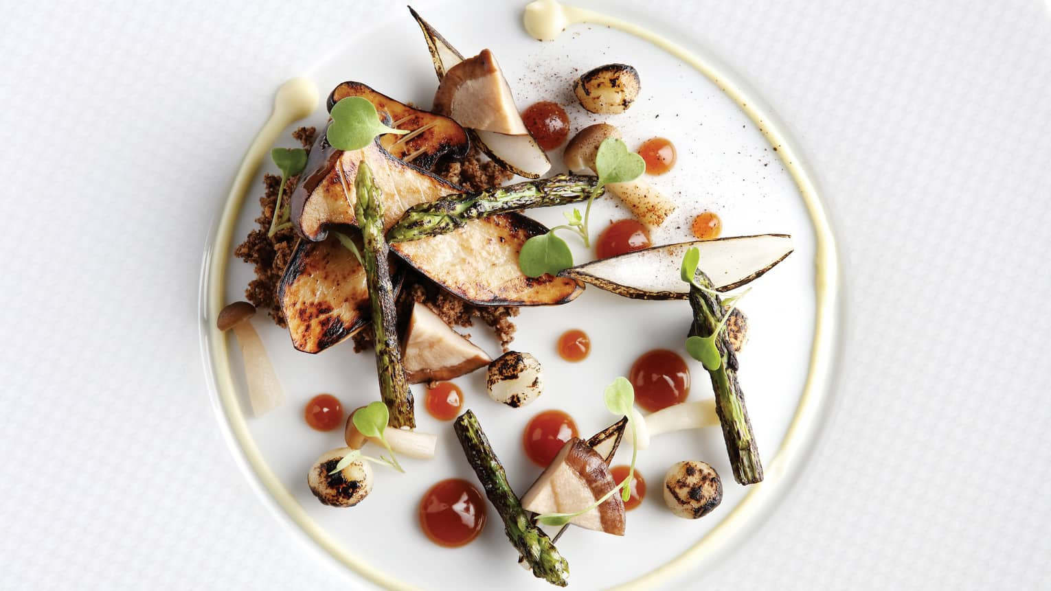 Grilled King Oyster Mushrooms, asparagus and mushrooms on white plate