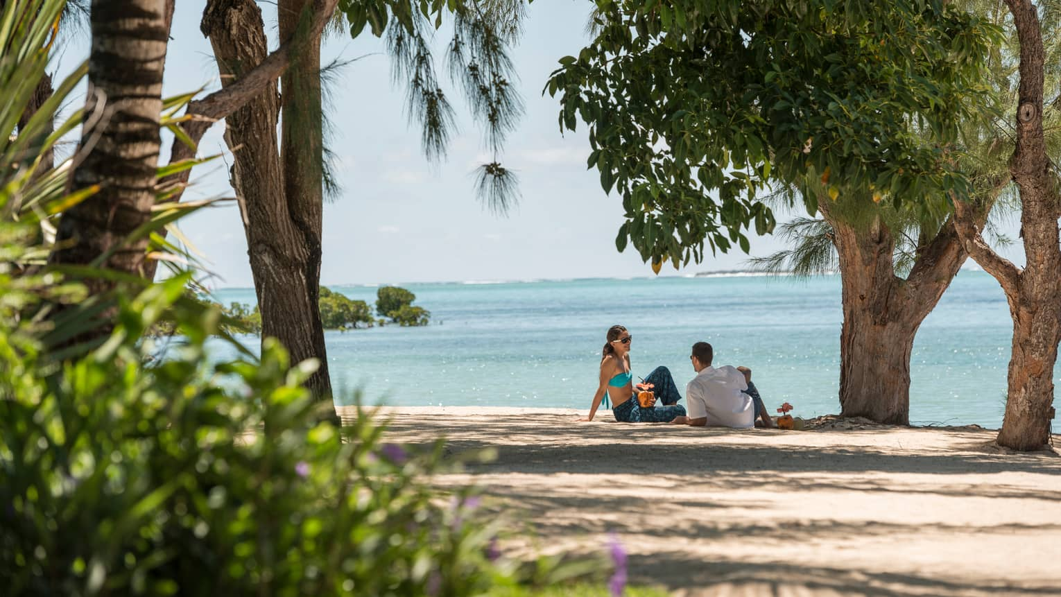 Couple sit on sand beach with cocktails under shade of tall trees