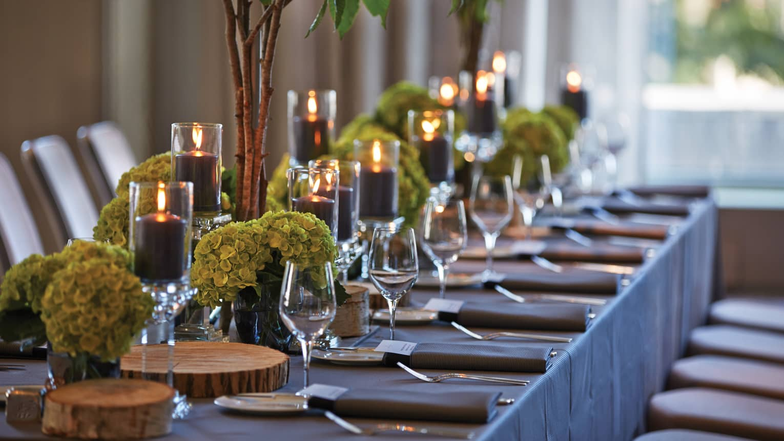 Black pillar candles in votives, green flowers, wine glasses along banquet table