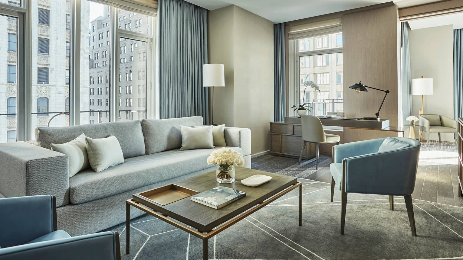 Gotham Suite with Terrace long grey sofa, blue chairs, desk, corner windows with city views