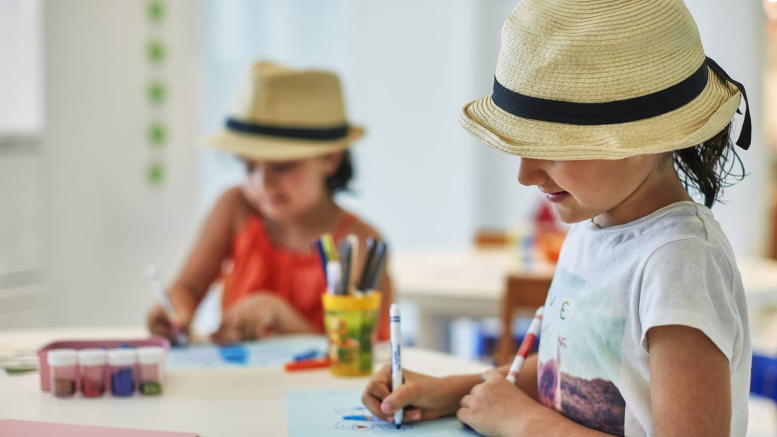 Two smiling children wearing straw fedora hats colour pictures with markers at craft table