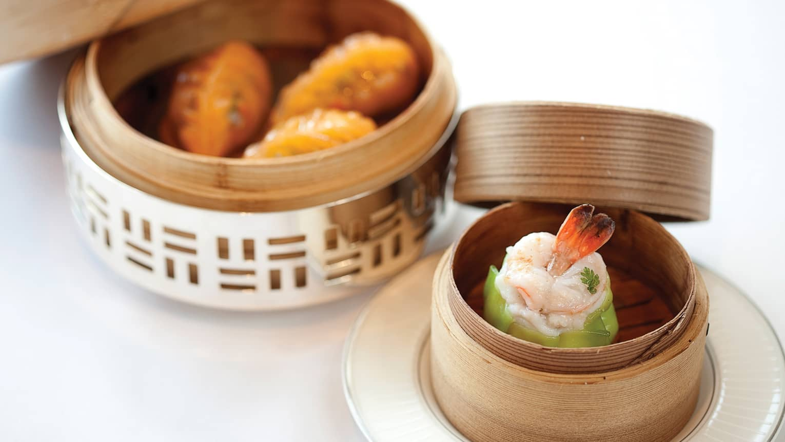 Two bamboo baskets with steamed lobster, dumplings