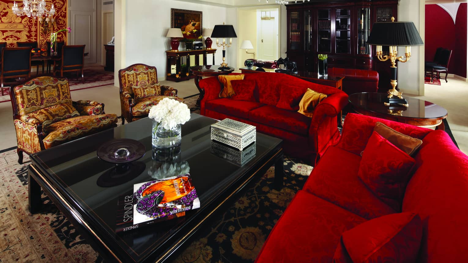 Presidential Suite with red satin sofas, red-and-gold armchairs, large black coffee table with books, flowers
