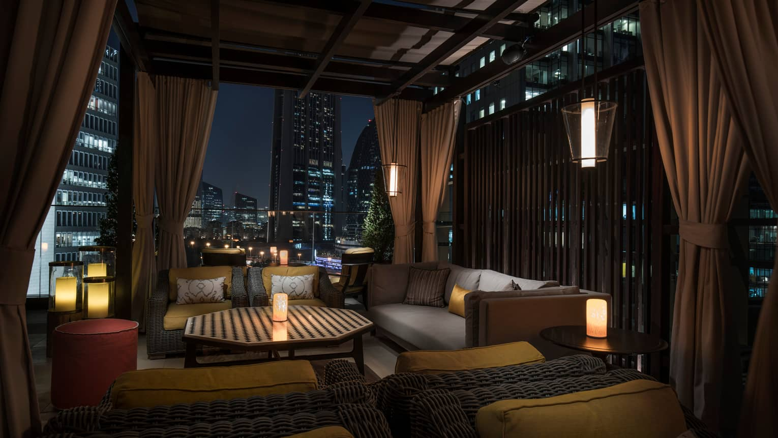 Outdoor patio lounge area at night with candles, plush cushions, wood roof