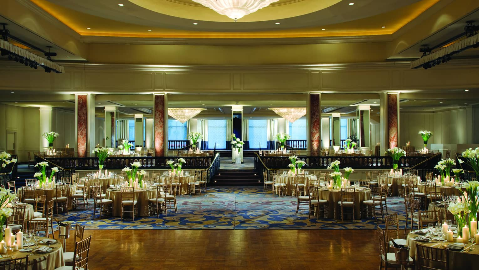 Ballroom dance floor under large cone-shaped crystal chandelier, round banquet tables