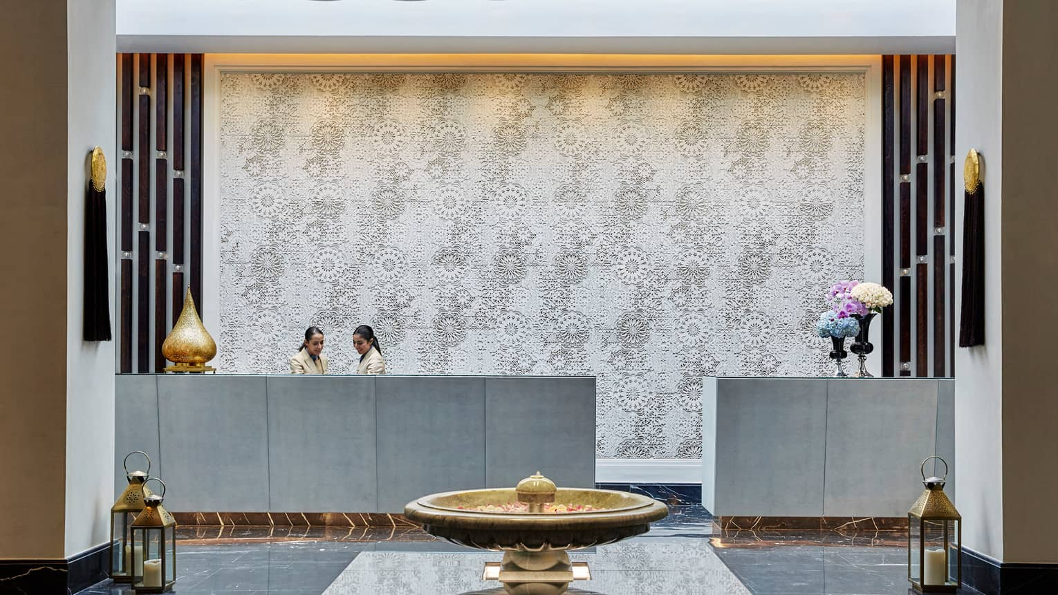 Staff at hotel reception desk in lobby with white mosaic backdrop