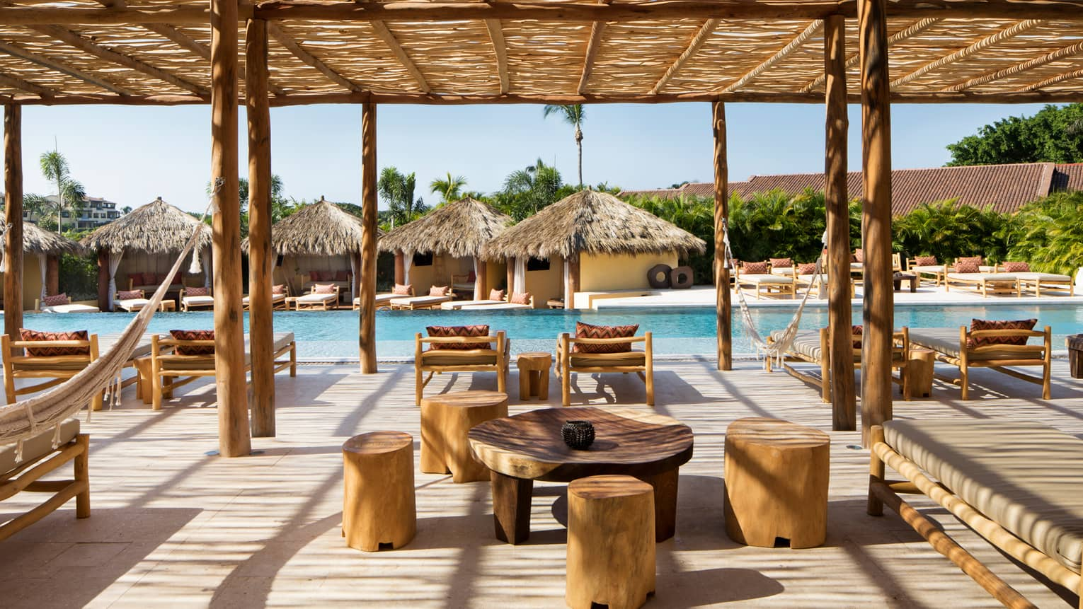 Tamai Pool Complex outdoor dining lounge with rustic wood stools and table, hammocks, lounge chairs