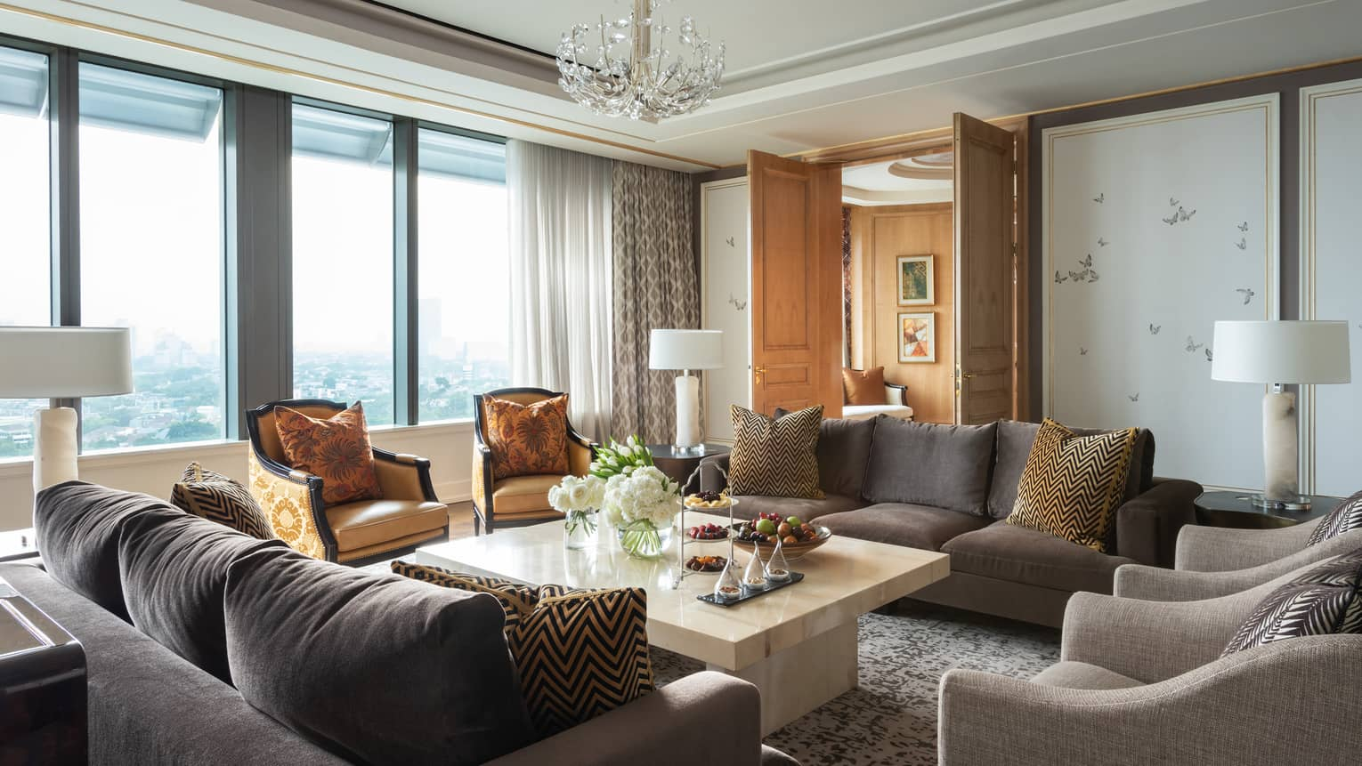 Hotel suite seating area with two plush sofas and four armchairs by sunny window