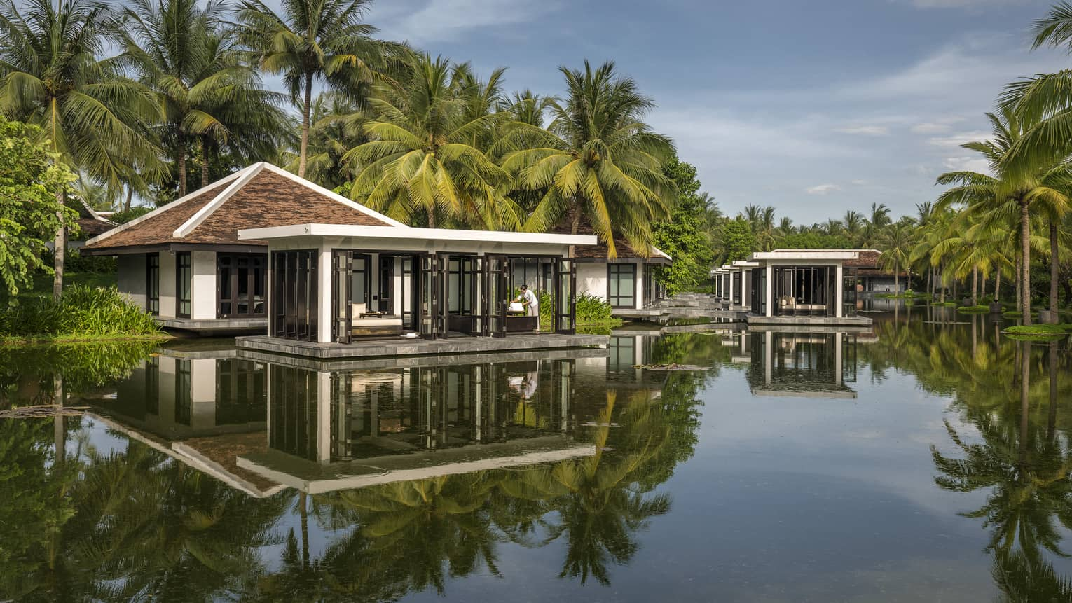 Overwater Heart of Earth spa villa staff folds white towels on deck, reflection in water