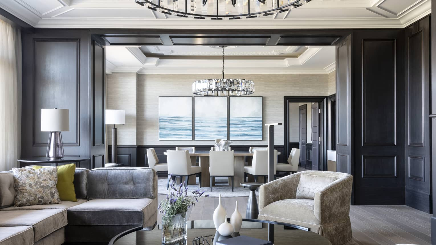 Presidential Suite's living room features dark wood-panelled walls, opening to the dining room