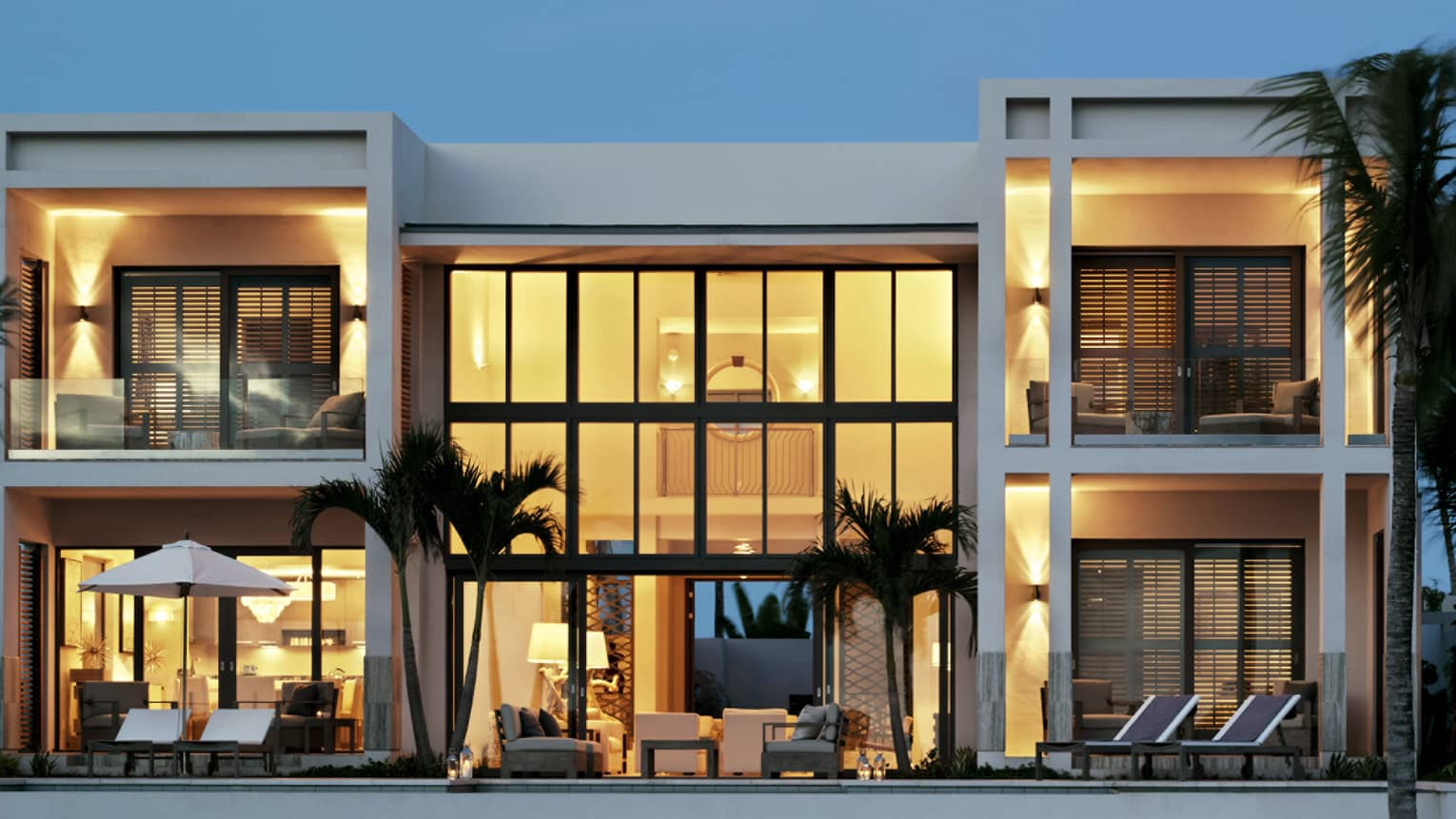 Exterior view of five-bedroom, white beachfront villa at dusk, two storeys with floor-to-ceiling illuminated windows