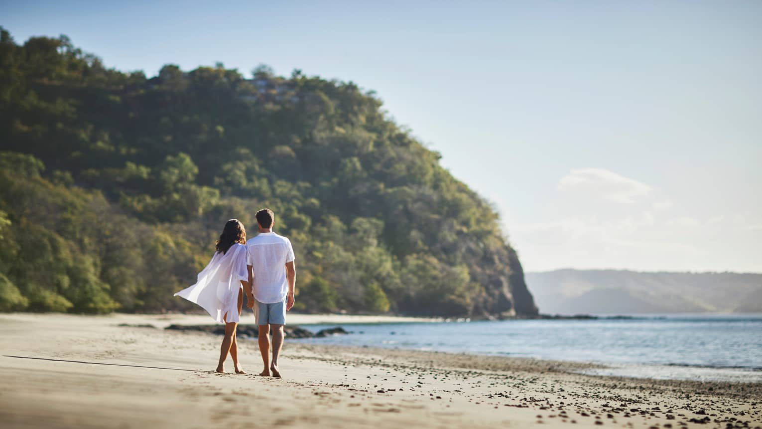 Back of man and woman in sheer white shirt walking barefoot on sandy beach, mountains in background