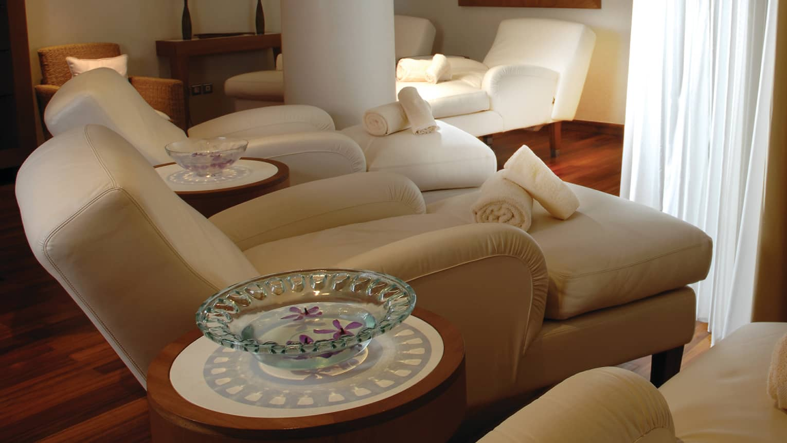 Three large plush chaise lounge sofas in dimly-lit spa room, rolled white towels