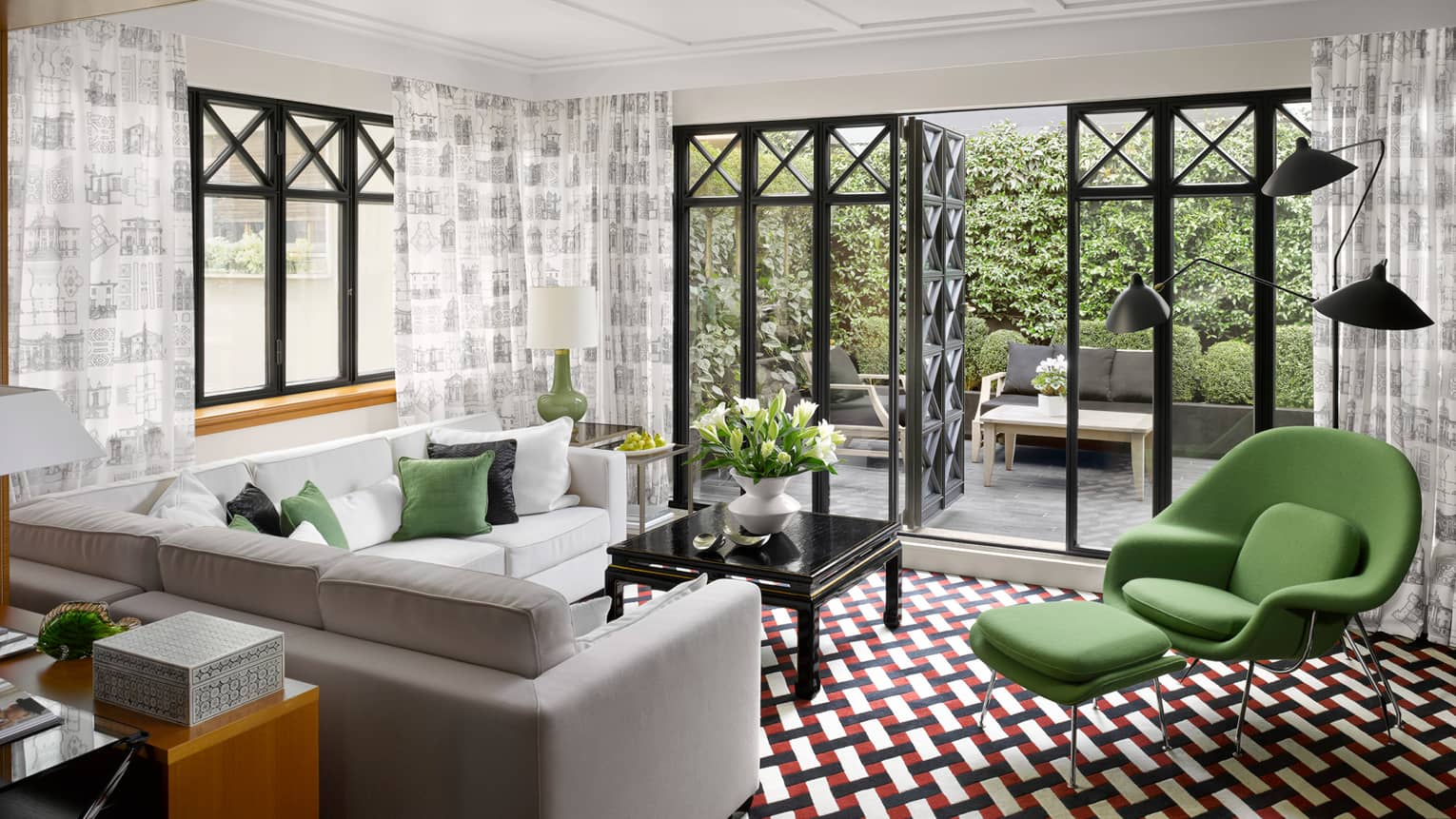 Fashion Suite grey, white sofas, green armchair on retro-style red-and-black tile floor, open balcony doors