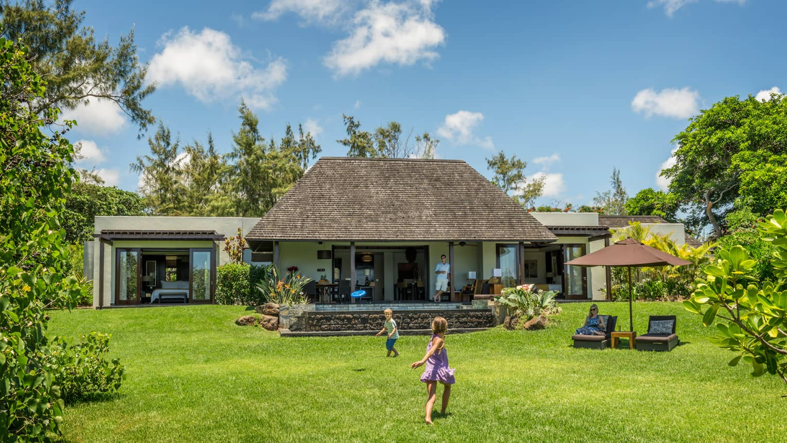 Young children play on green lawn in front of bungalow as dad watches from covered patio