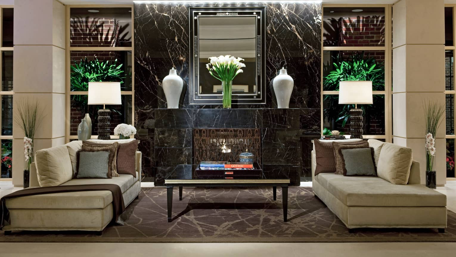 Lobby with plush chaise sofas, pillows by black marble fireplace mantle with large white vases, fresh flowers