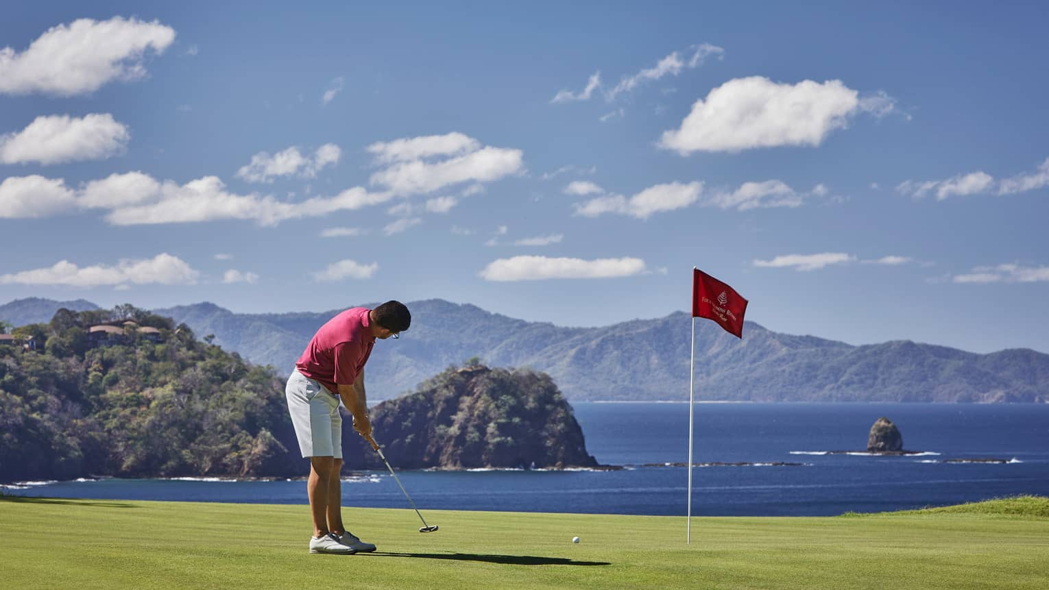 Man prepares to putt near red flag on golf green overlooking ocean