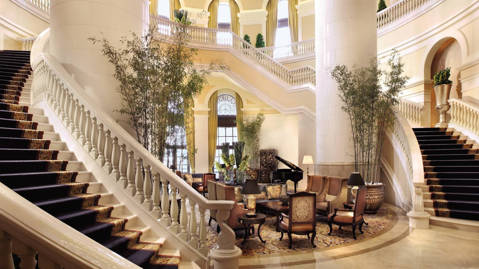 Hotel lobby with two grand staircases around large white pillars, seating area