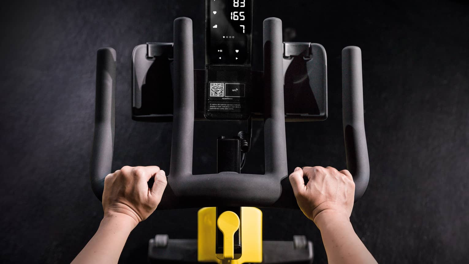 Close-up of hands holding black bars of cardio machine in dark room