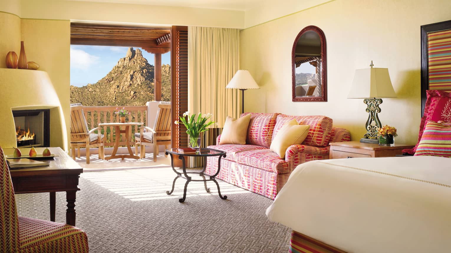 Deluxe Casita Room corner of bed, pink patterned loveseat and table by open balcony door, mountain view