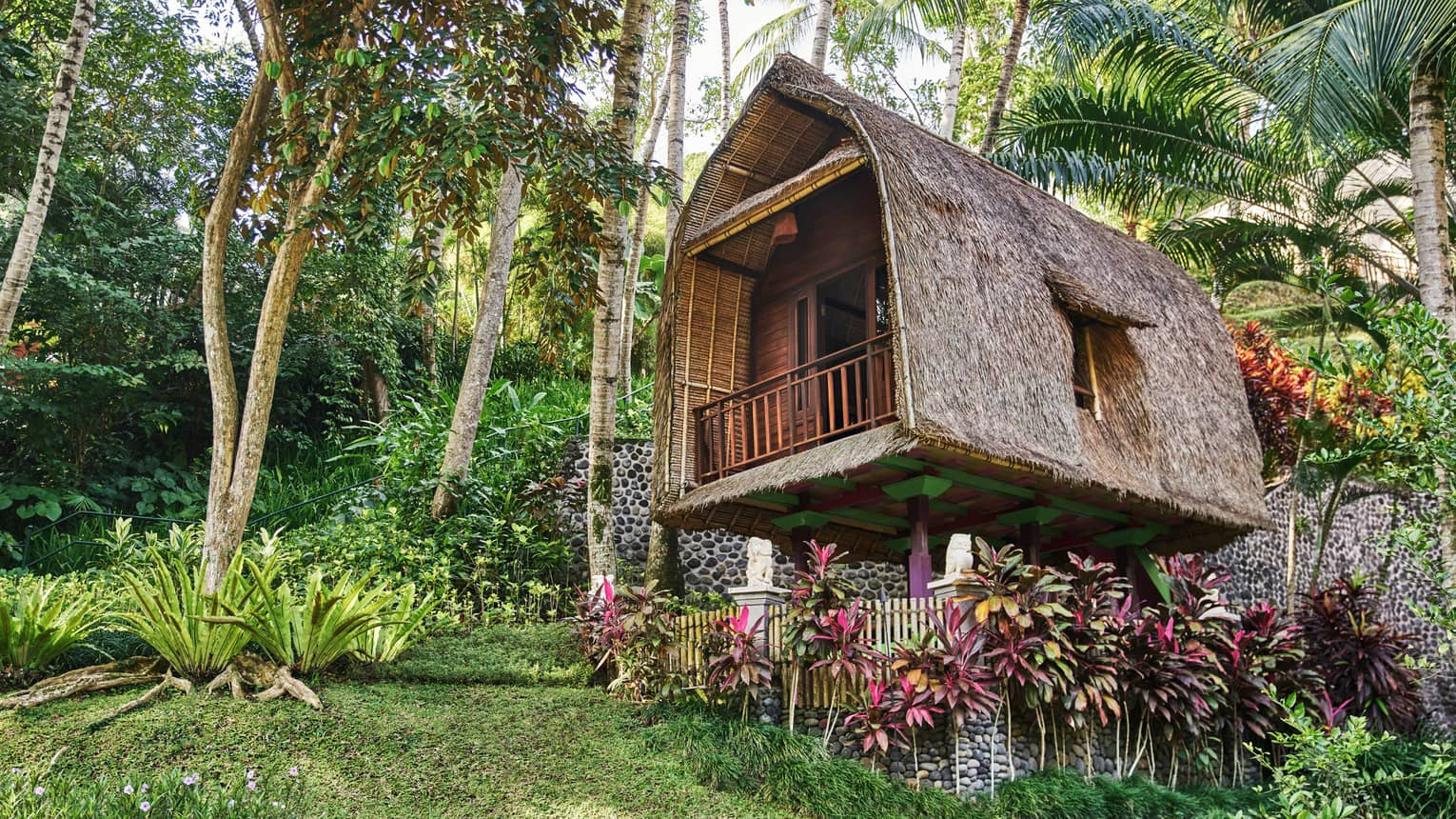 Exterior view of rice barn tree house with curved, A-frame structure, thatched roof, surrounded by tropical foliage