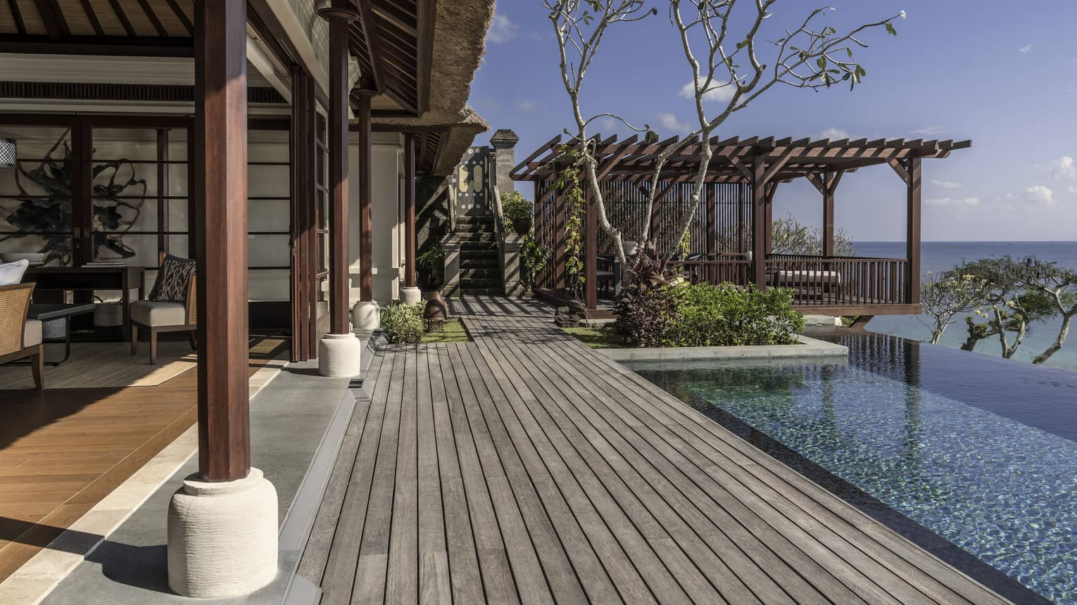 Royal villa wood patio boards, wood pillars, infinity pool looking out at ocean