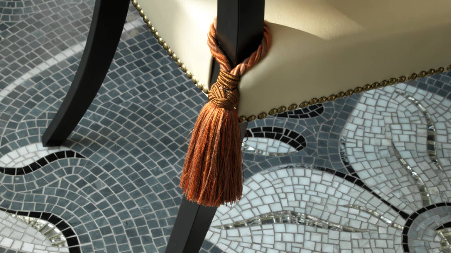 Close-up of rust-coloured tassel tied around arm of dining chair, mosaic tile floor below