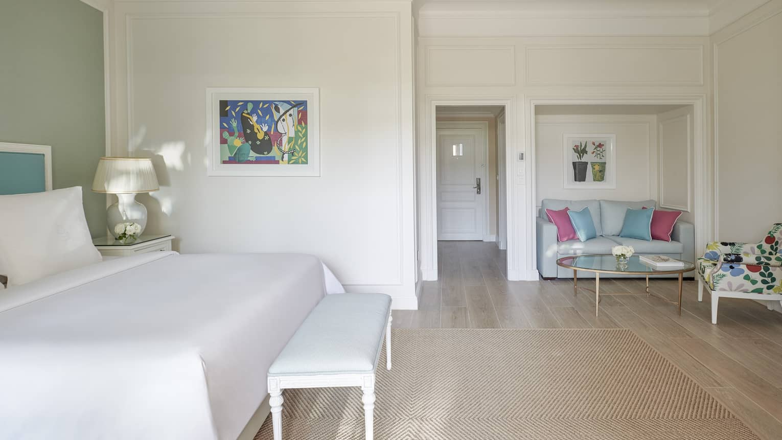 White room, white bed with blue headboard on green wall, foot bench, wood floor, seating area