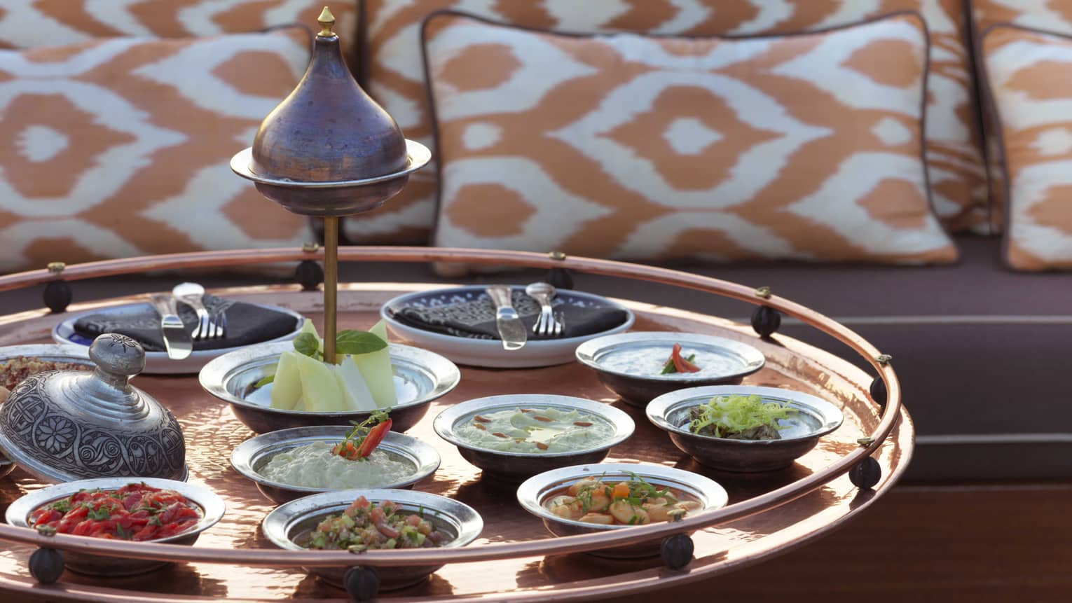 Mezze appetizers in small dishes on large brass tray