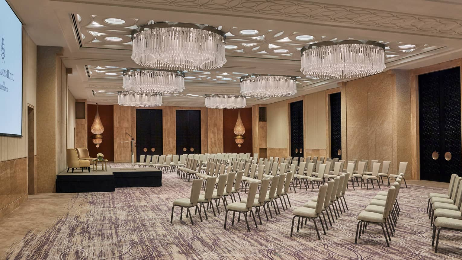 Rows of chairs face small stage in Atlantique ballroom with large chandeliers