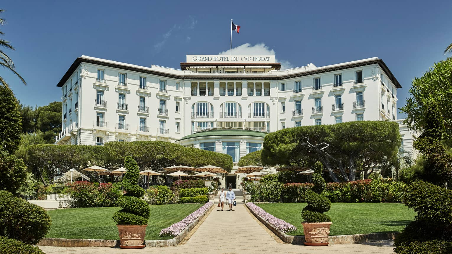 Two people walk down sunny stone path under large Grand-Hotel du Cap-Ferrat