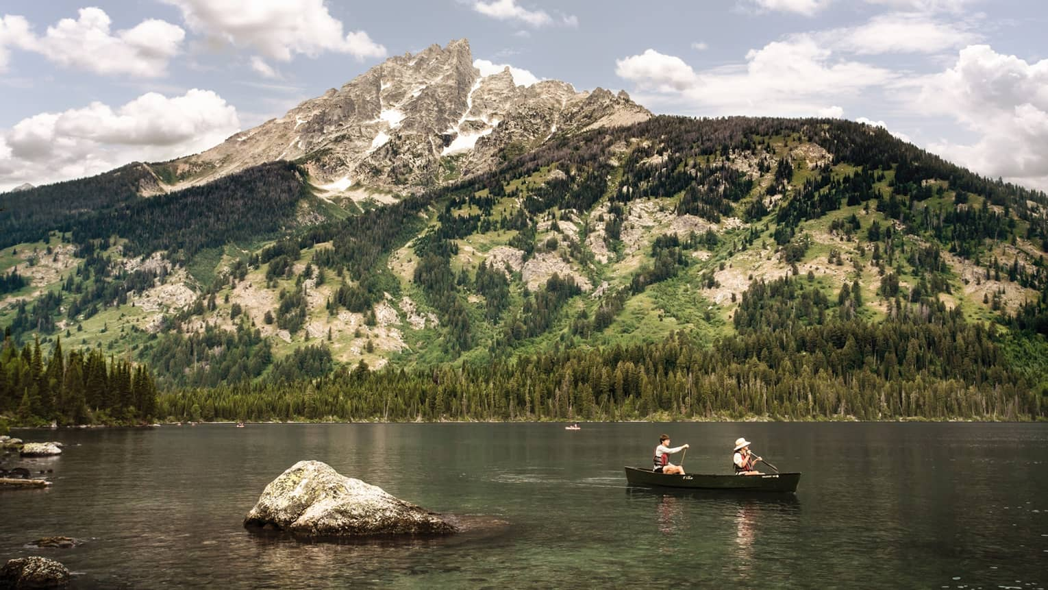 Two people in canoe on lake below towering mountains on sunny day