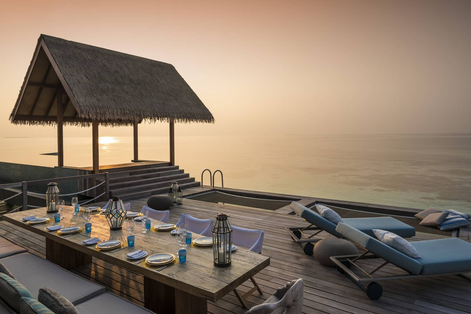 Two-Bedroom Water Villa thatched roof pavilion over long private dining table on deck at sunset