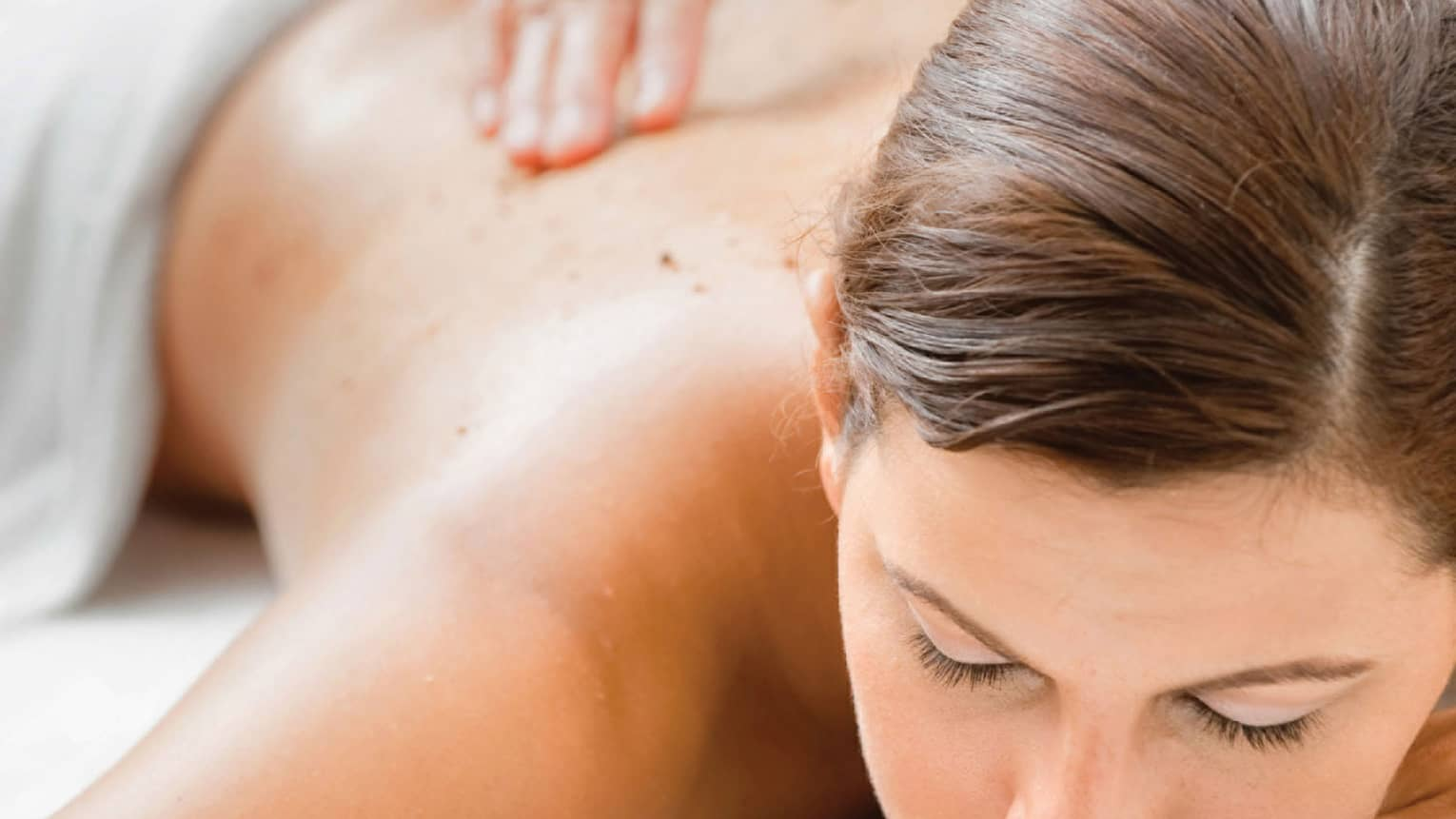 Woman closes eyes as spa staff massages her back