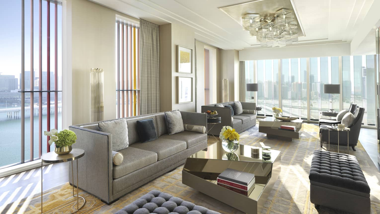 Presidential Suite with grey sofas and ottomans, floor-to-ceiling corner windows with sunny Gulf views