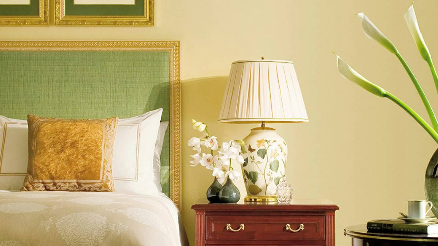 Close-up of Superior City-View Room bed with green headboard, gold frame and accent pillow, bedside lamp and orchid