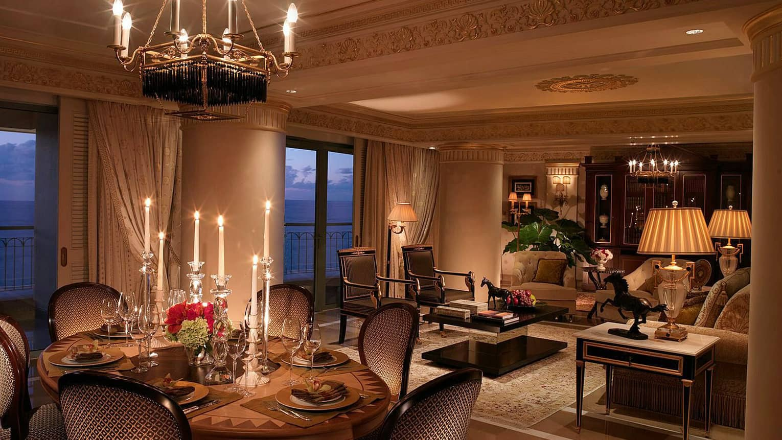 Dimly-lit Royal Suite dining room at night with tall candles beside seating area with sofas, horse statues, sea view