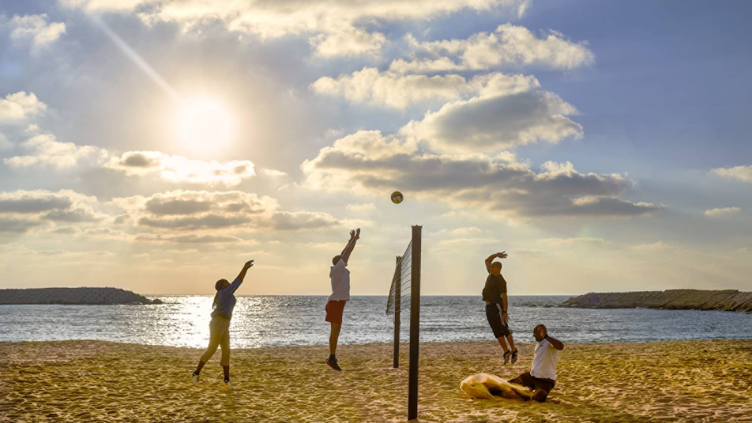 A group of four play volleyball on the beach at four seasons hotel alexandria.