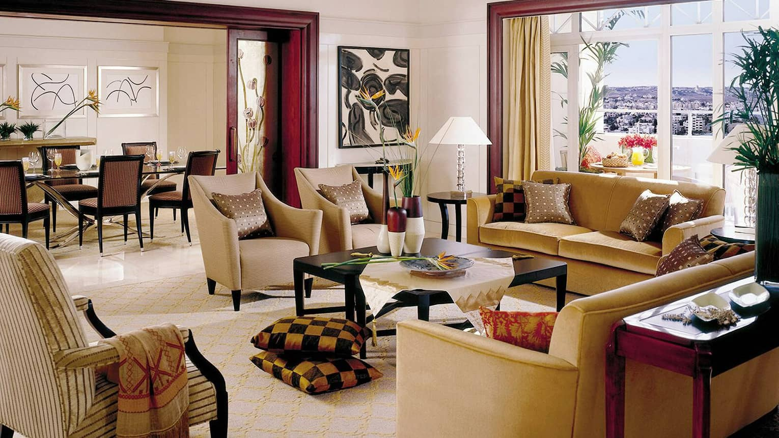 Living room with two taupe chairs, two golden fabric sofas, large square coffee table, windows